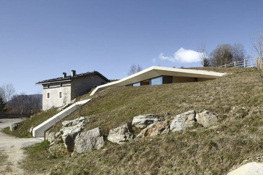 white concrete home with green roof