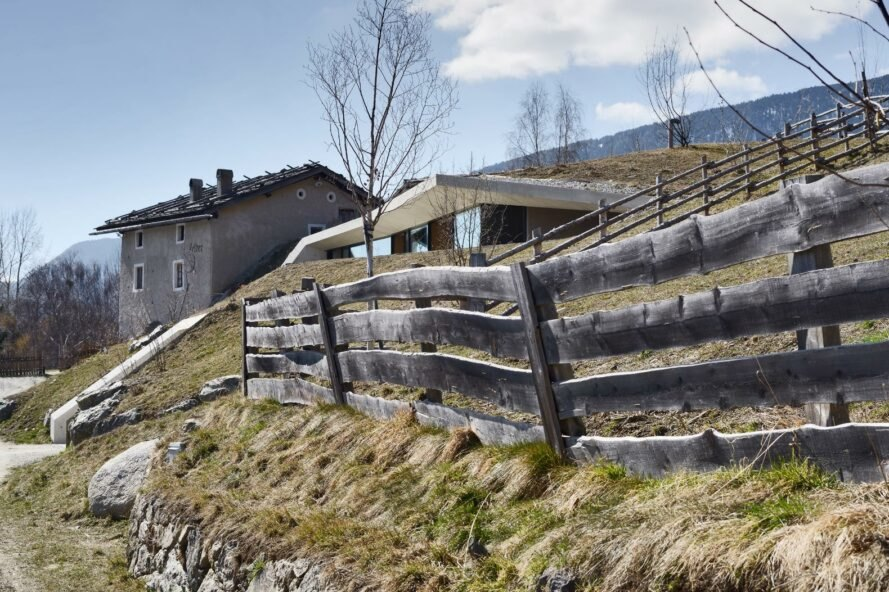 rustic wood fence outside concrete home buried in a hill
