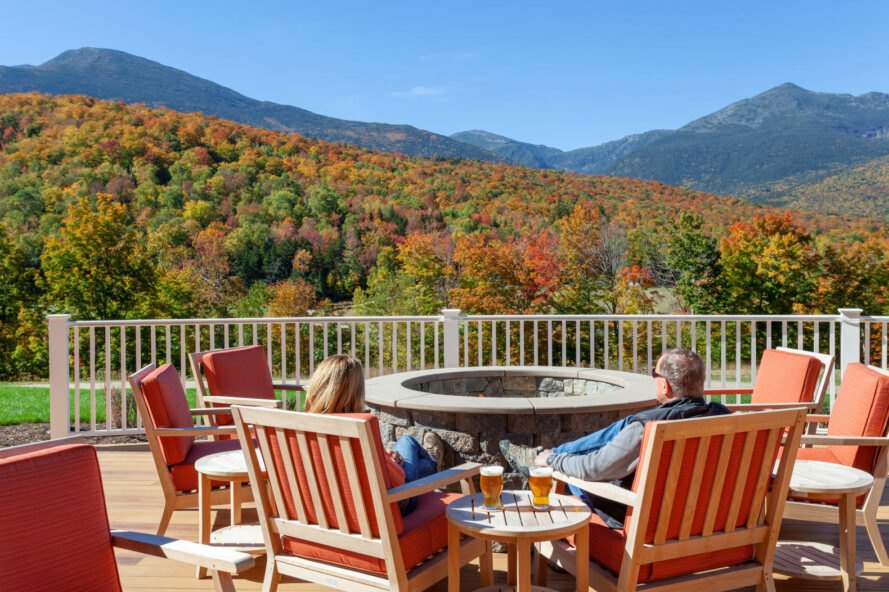 Guests sit by a firepit and look at the fall colors on the mountains.