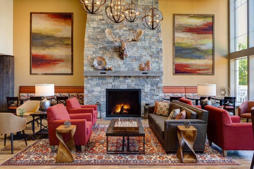 lobby with red and brown seating and large stone fireplace