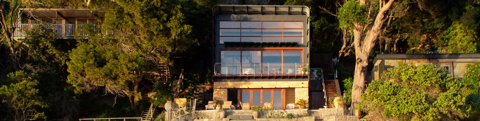 home with glass facade built on shoreline