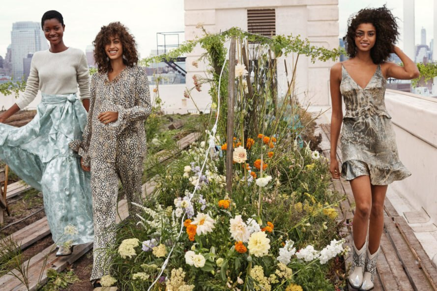 three models in gray and blue outfits in a garden