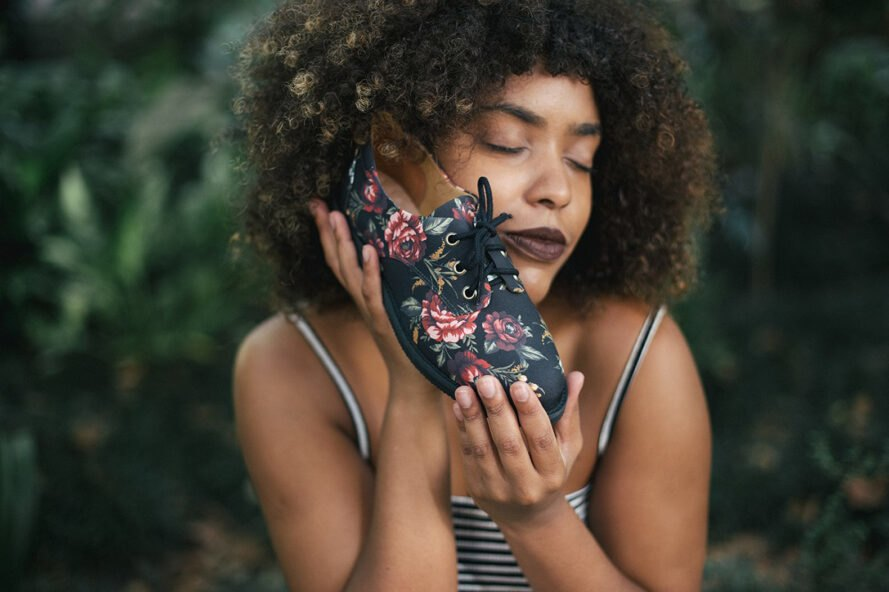 person holding a vegan shoe with a floral print
