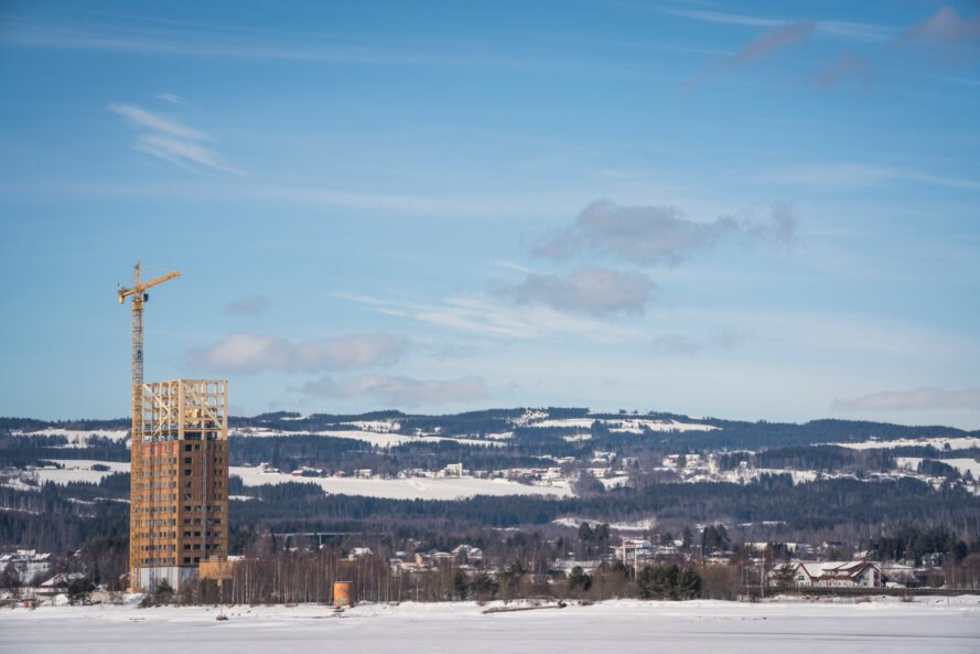 tall wood building under construction with snow-capped mountains in distance