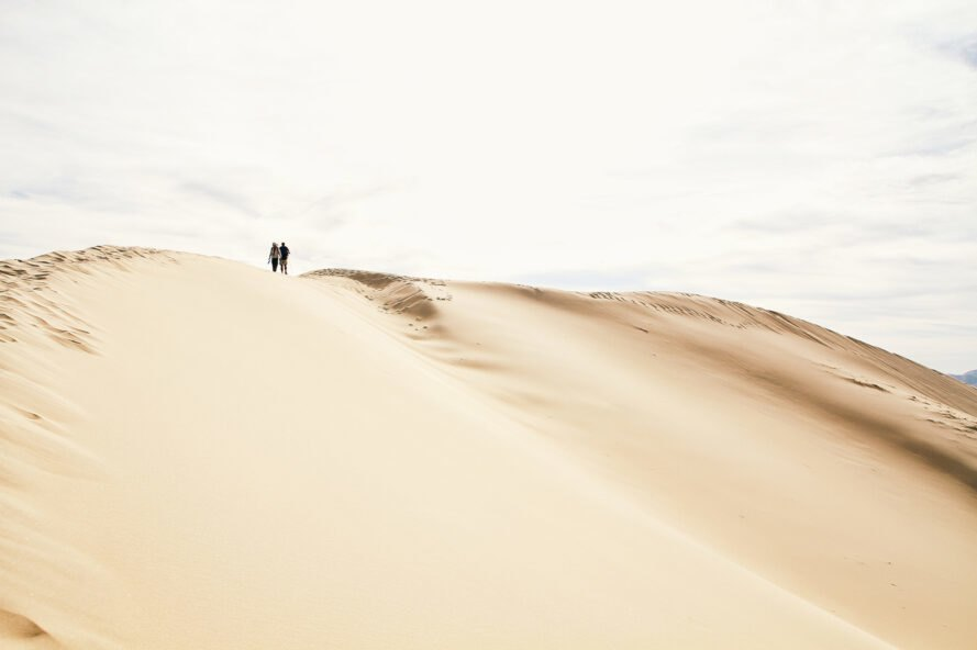 two people walk on sand dunes