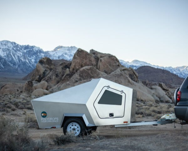 geometric metal trailer in front of mountains