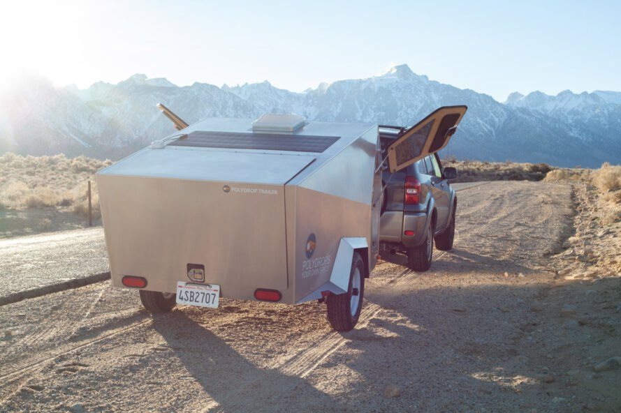 geometric metal trailer with open doors parked in front of mountains