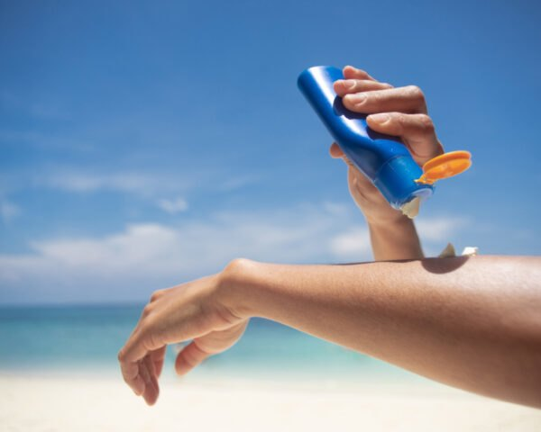 a person applies sunscreen to their arms at the beach