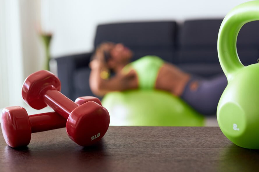 two red weights are placed on a wooden table with a woman exercising in the background near couch