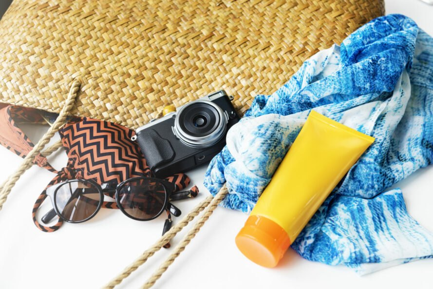 brown beach bag with camera blue scarf and yellow sunscreen