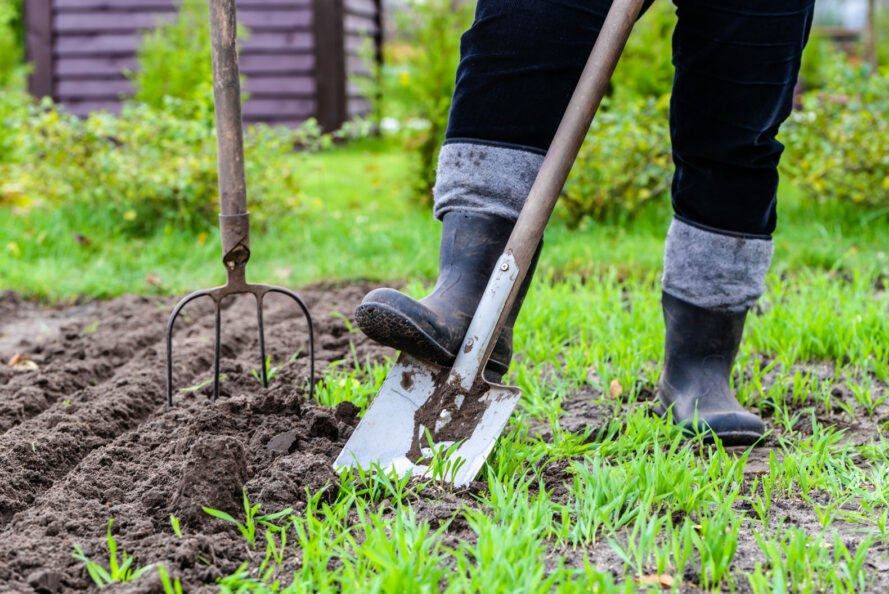 person digging into ground with shovel and rake