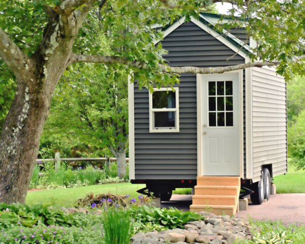 tiny home on wheels surrounded by trees and greenery