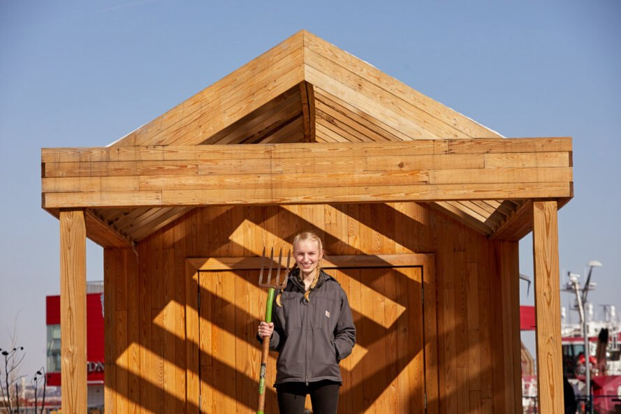 woman with pitchfork in front of wood garden shed