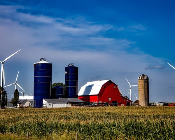 wind turbines beside red barns and silos