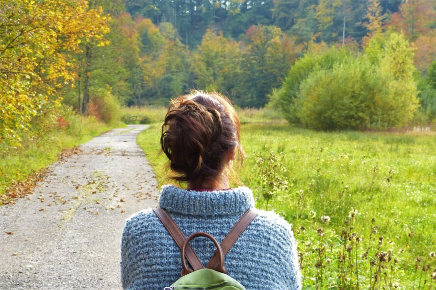 woman walking along a paved pathway surrounded by nature