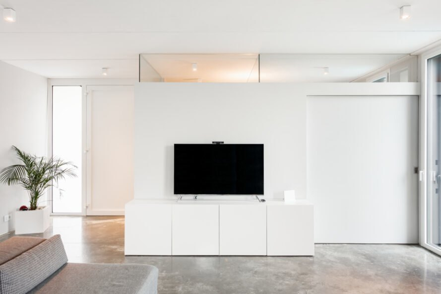 all white living space with tv on white consol