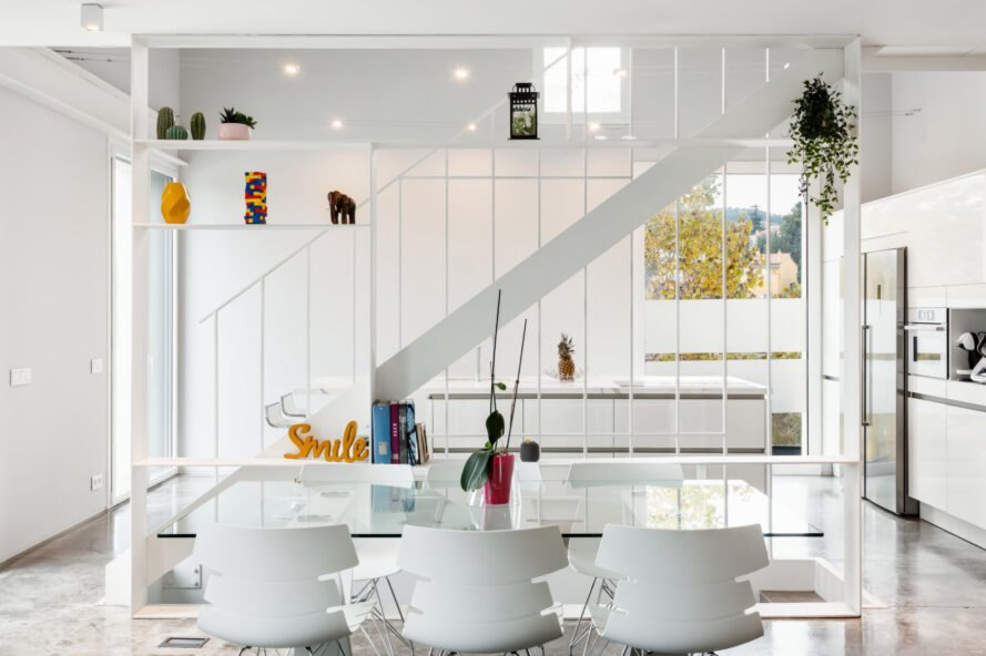 all white living area with glass dining table and white chairs