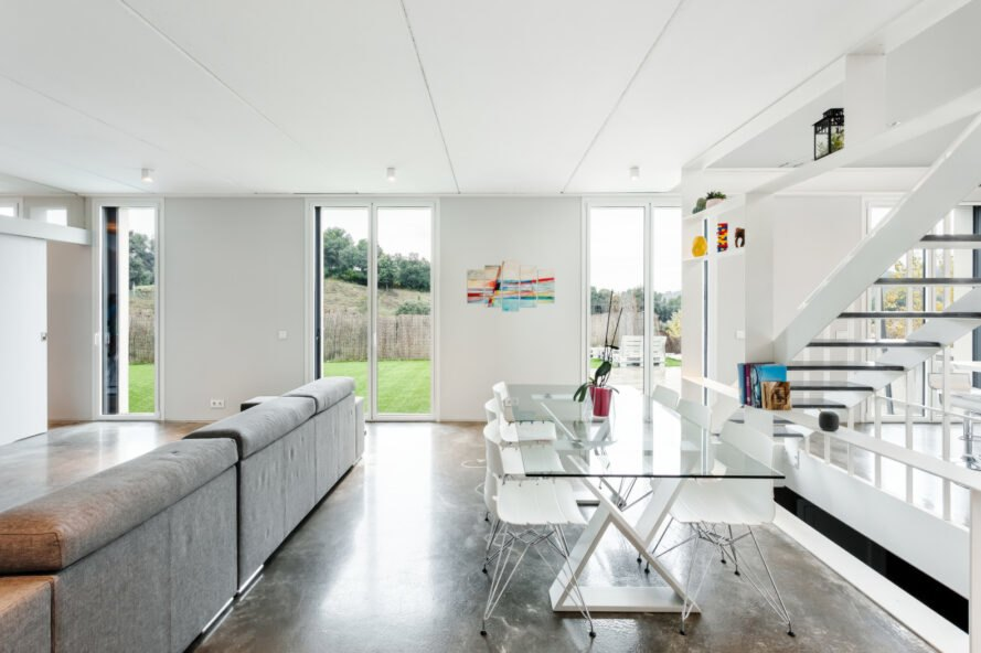 all white living space with glass dining table