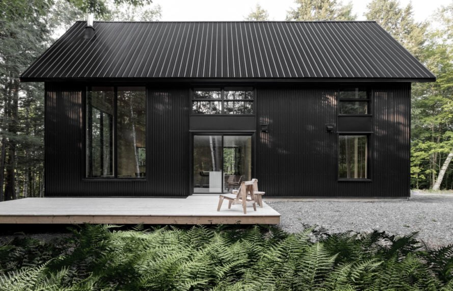 black cabin with wooden deck