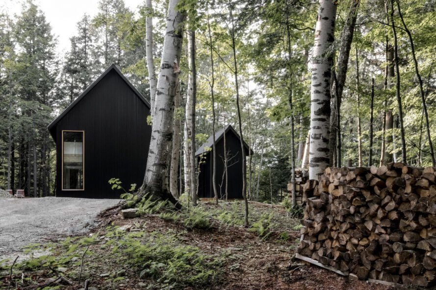 two black cabins in a forest