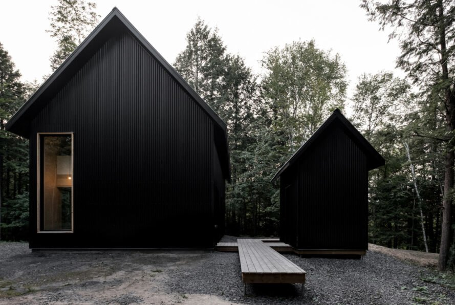 two black cabins with pitched roofs