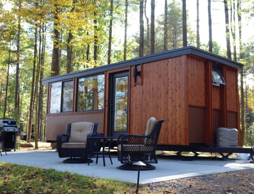 wooden tiny home with concrete deck and seating area
