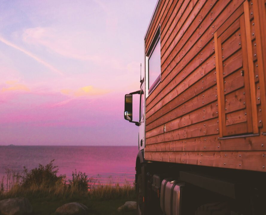 up-close shot of wooden cladding on motorhome with pink sunset in the distance