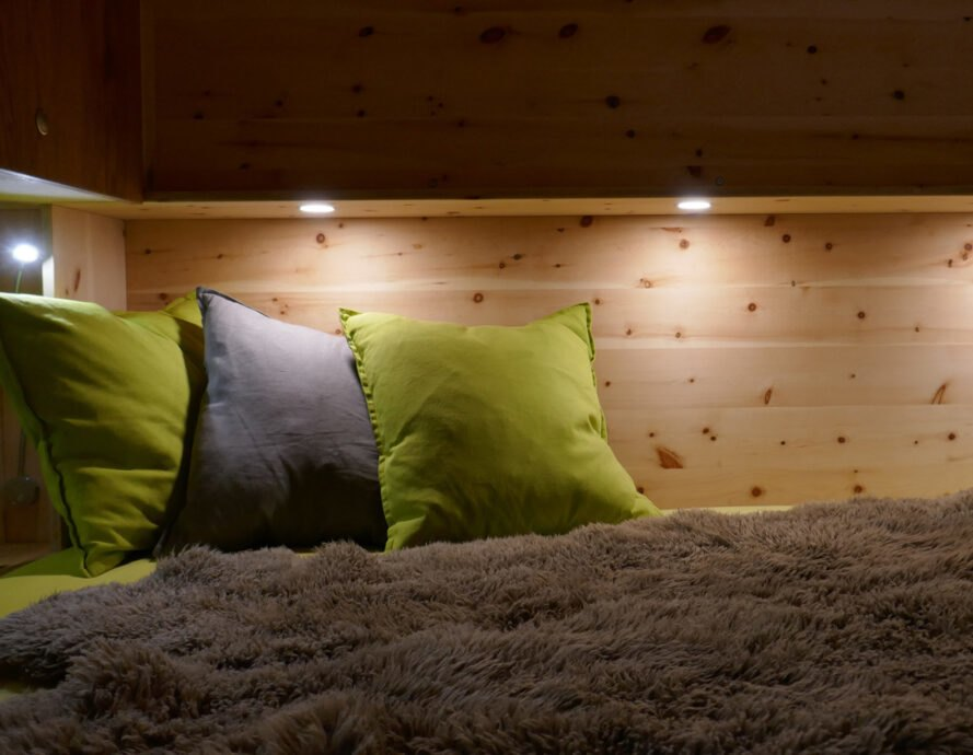bedding area with wood walls and recessed lighting