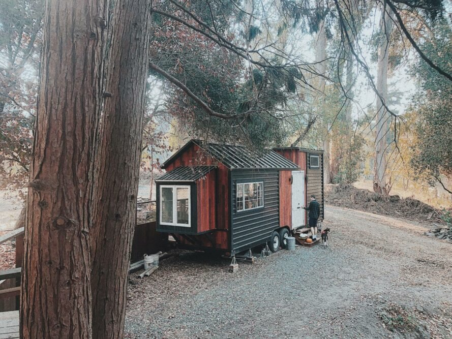 metal and wooden tiny home with man outside