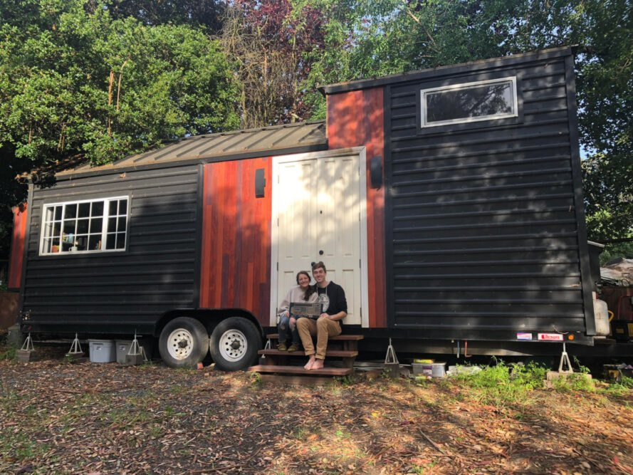 couple sitting in front of their tiny home