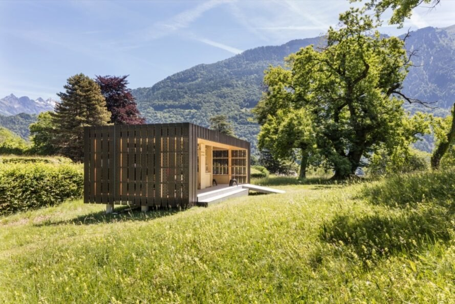 small prefabricated pop up pavilion is surrounded by trees and greenery