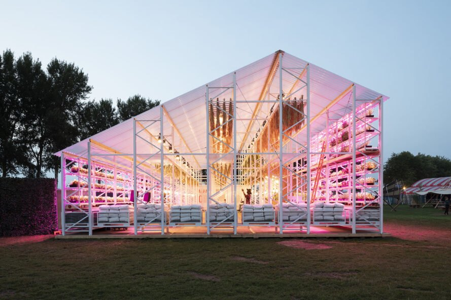 white gabled open-air structure lit up pink inside
