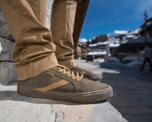 person wearing brown shoes standing on pavement with snow in the background