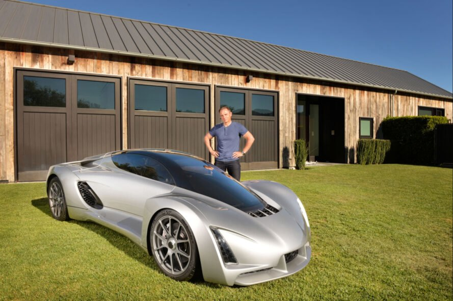 man standing next to a 3d printed silver car