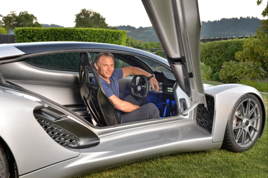man sitting in a 3d printed silver car