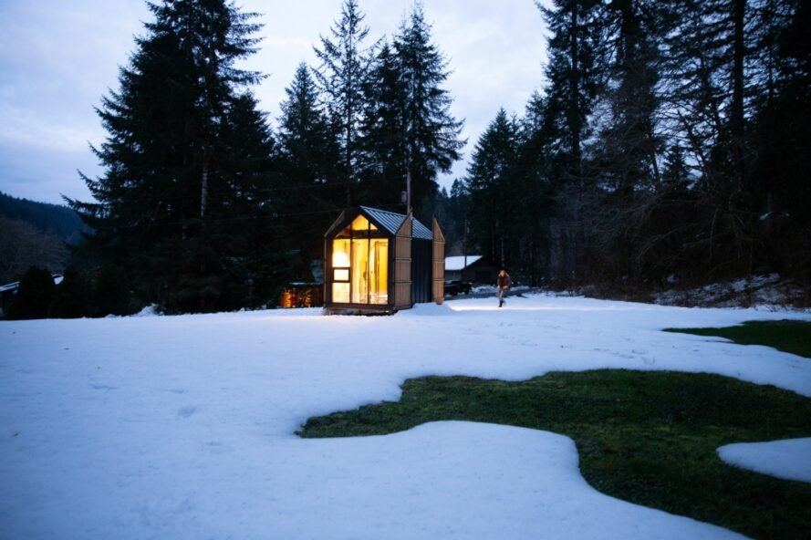 tiny cabin with pitched roof and glazed facades lit from within