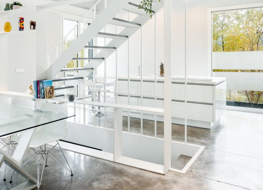 all white living area with steel staircase