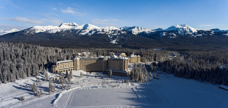 hotel with mountains in the background surrounded by trees and snow
