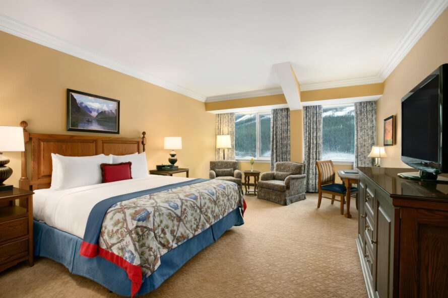 view of a suite with large bed and light brown colored carpet with large windows showing mountain views