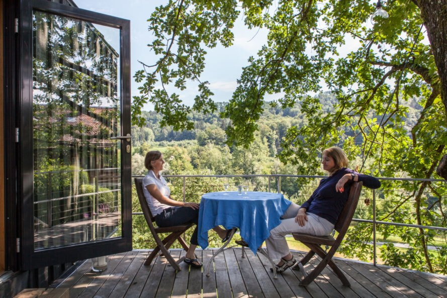 two people sitting at round table on treehouse deck