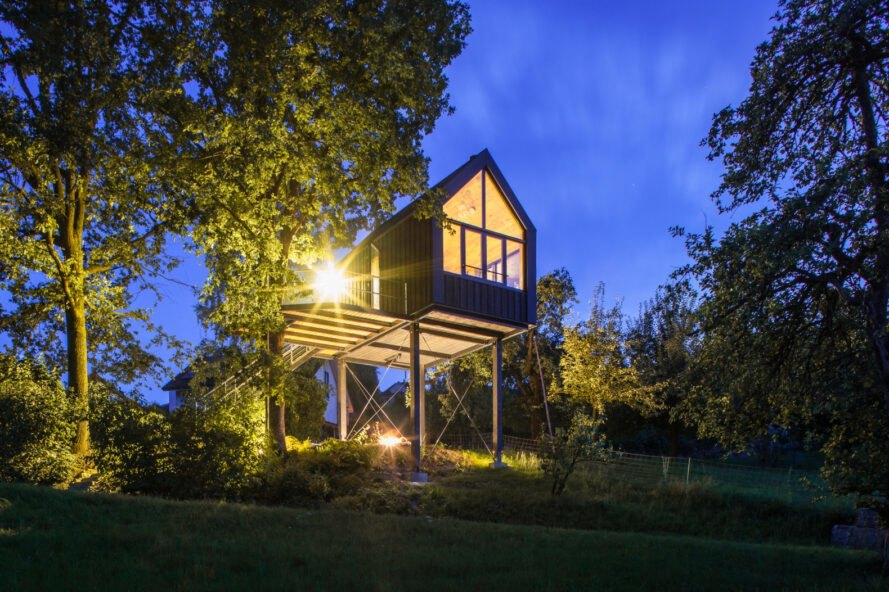black gabled treehouse lit from within at night