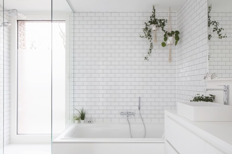 white tiles and walls adorn the bathroom with plants placed near tub