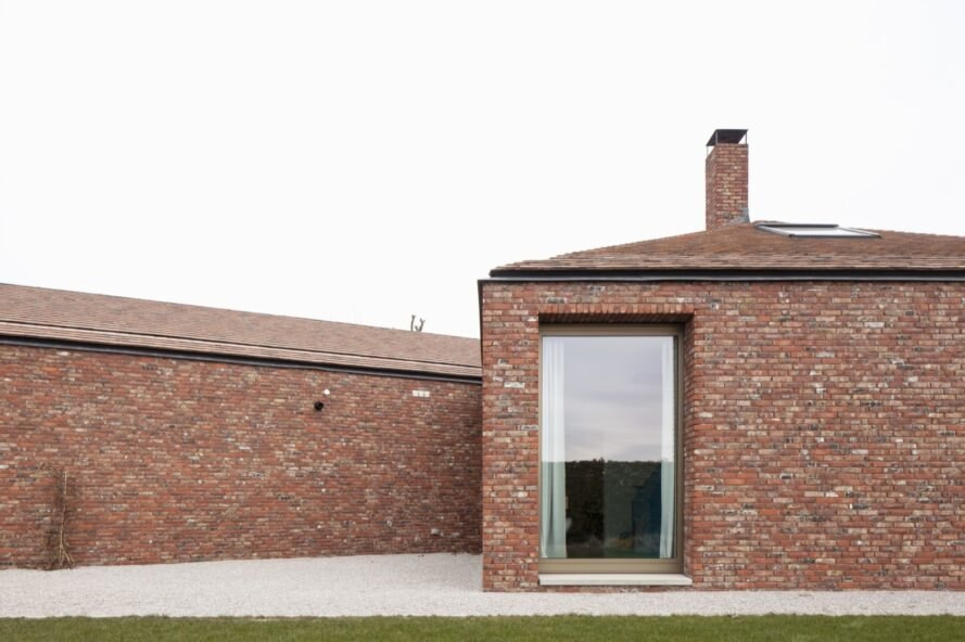 brick house with large ceiling to floor windows surrounded by grass