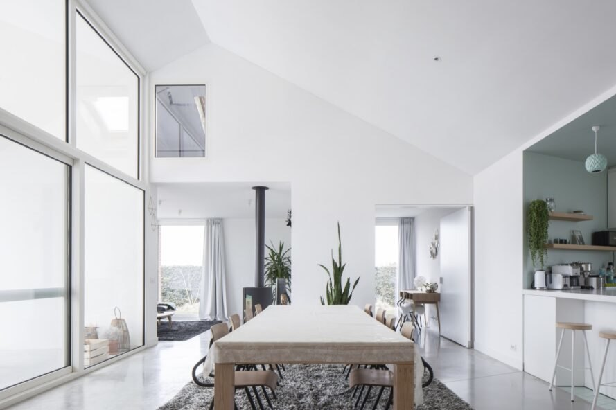 large wood table in dining room surrounded by white walls and minimalist designs and plants