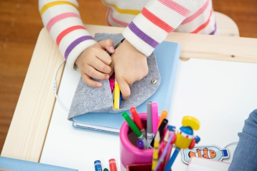 child putting markers inside a pencil pouch