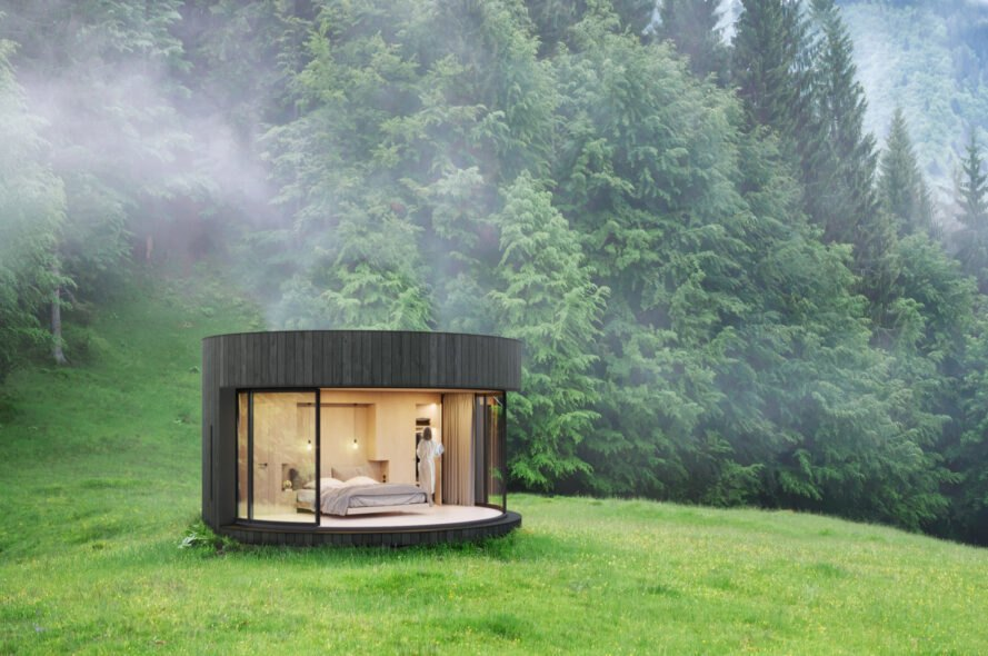 round wood cabin with glass facade on green landscape