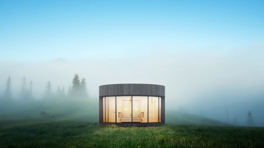 round cabin lit from within in a foggy landscape
