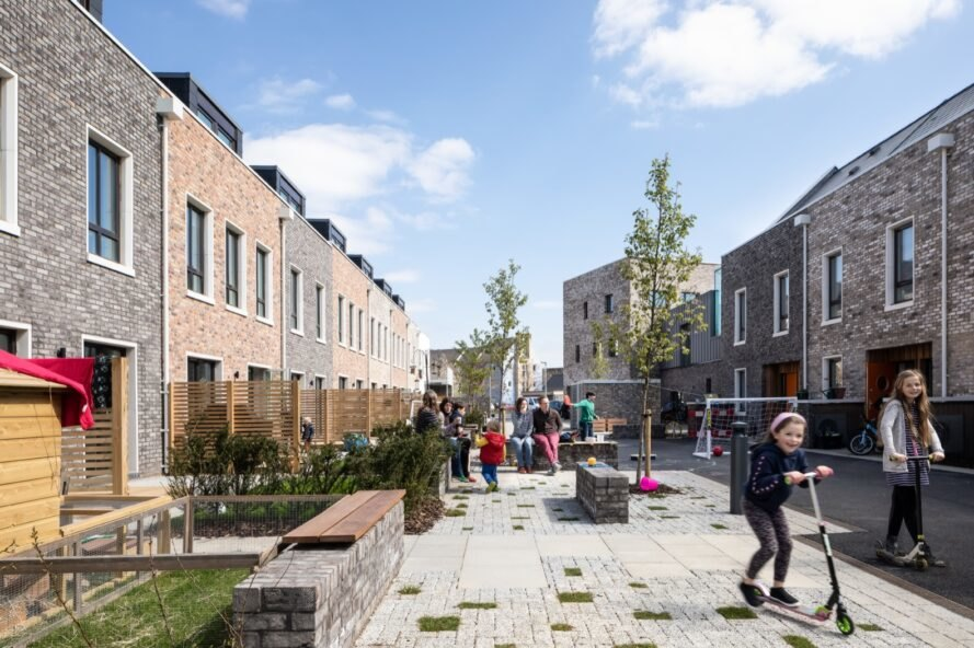 inside the cohousing area with nearby gardens and children playing