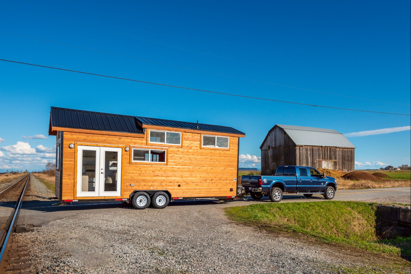 A tiny home on wheels with brilliant interiors and two lofts can be yours for $56K