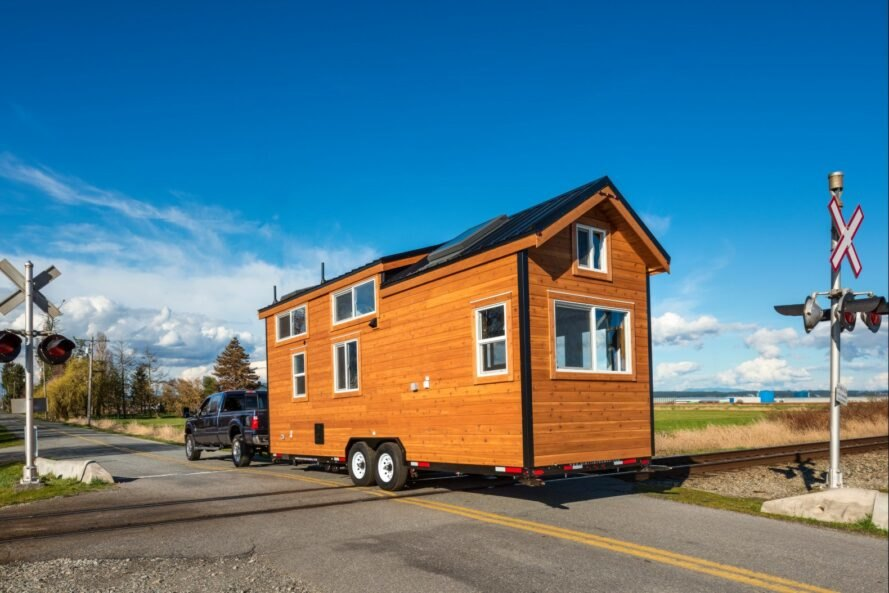 tiny wooden home with pitched roof pulled by blue truck